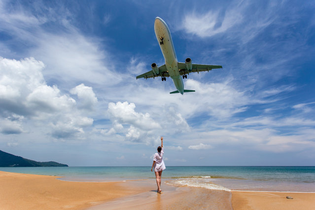 Portrait beautiful woman on the beach, Landing aircraft above the beach at Phuket Airport. Mai Khao beach, one of the most popular beaches among tourists in Phuket. (Photo by Southtownboy/Getty Images/iStockphoto)