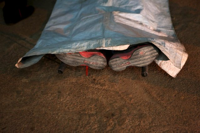 A corpse is seen outside the Radisson hotel in Bamako, Mali, November 20, 2015. Around 27 people were reported dead on Friday after Malian commandos stormed a hotel seized by Islamist gunmen to rescue 170 people, many of them foreigners, trapped in the building. (Photo by Joe Penney/Reuters)