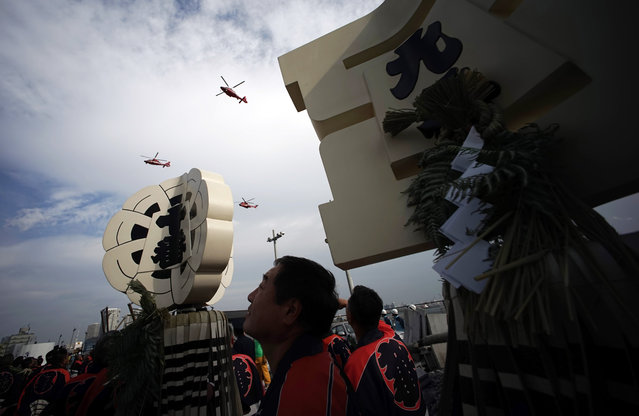 Members of a traditional firefighting preservation group wait to perform as helicopters from fire department fly over during the annual New Year's Fire Brigade Review in Tokyo, Tuesday, January 6, 2015. (Photo by Eugene Hoshiko/AP Photo)