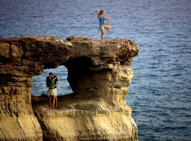 "A couple kiss, as another tourist poses for photographs, at ""The Caves"" cliffs situated along the Mediterranean Sea on the southeast coast of Cyprus. (Photo by Patrick Baz/AFP Photo)"