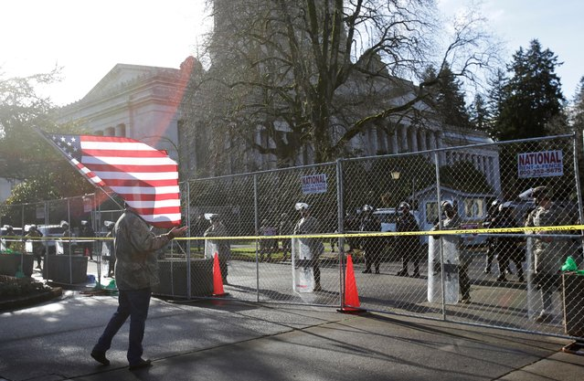 A man holding a U.S. flag stands in front of members of the Washington National Guard outside the Capitol Building ahead of rallies the day before a legislative session begins in Olympia, Washington, U.S. January 10, 2021. (Photo by Lindsey Wasson/Reuters)
