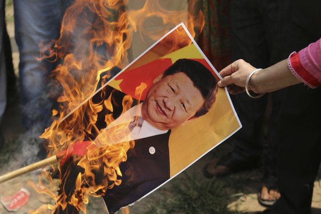 A Bharatiya Janata Party activist burns a photograph of Chinese President Xi Jinping during a protest in Jammu, India, Wednesday, July.1, 2020. Indian TikTok users awoke Tuesday to a notice from the popular short-video app saying their data would be transferred to an Irish subsidiary, a response to India's ban on dozens of Chinese apps amid a military standoff between the two countries. The quick workaround showed the ban was largely symbolic since the apps can't be automatically erased from devices where they are already downloaded, and is a response to a border clash with China where 20 Indian soldiers died earlier this month, digital experts said. (Photo by Channi Anand/AP Photo)