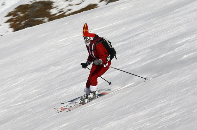 A woman, dressed as Santa Claus, takes a curve during a promotional event on the opening weekend in the alpine ski resort of Verbier, Switzerland, December 6, 2015. (Photo by Denis Balibouse/Reuters)