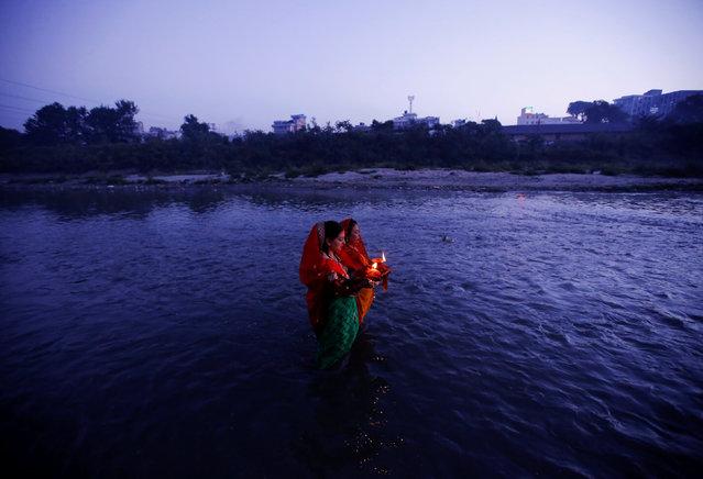 "Devotees offer prayers to the rising sun during the ""Chhat"" festival at Bagmati River in Kathmandu, Nepal November 7, 2016. (Photo by Navesh Chitrakar/Reuters)"
