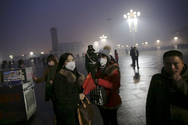 "People gather before the sunrise at the Tiananmen Square for a flag-raising ceremony amid heavy smog, after the city issued its first ever ""red alert"" for air pollution, in Beijing December 9, 2015. (Photo by Damir Sagolj/Reuters)"