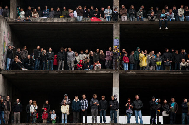 """Viewers"". People watching car racing event from abandoned building balconies. Curiosity to see Formula 1 race for the first time in Lithuania was bigger then the risk standing on the edge of the building ment to be demolished. By now it is destroyed. (Photo and caption by Ruta Balciunaite/National Geographic Traveler Photo Contest)"