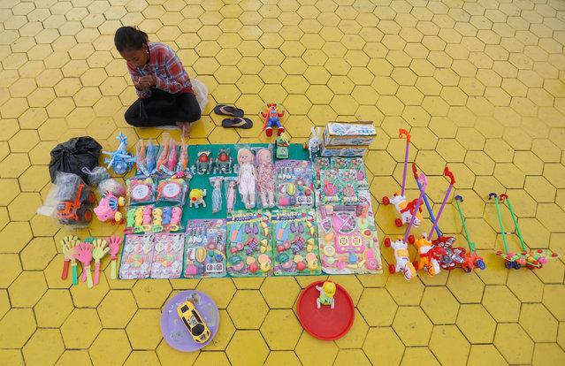 A girl sells toys in front of the Royal Palace in Phnom Penh, Cambodia, November 3, 2016. (Photo by Samrang Pring/Reuters)
