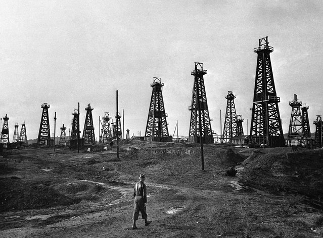 """A view of one of the many oilfields at Ploiesti in the Carpathian foothills of Romania on December 13, 1946. From the time that oil is """"struck"""" it is not seen until after it has been processed at the refineries miles away. The oil is pumped through pipes from the fields to the refineries. (Photo by Jim Pringle/AP Photo)"""