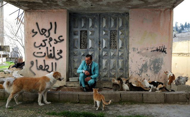 Ali Sarsour, an upholsterer, plays with his dog and cats as he wears one of his suits near his home in Amman, Jordan on February 6, 2021. (Photo by Alaa Al Sukhni/Reuters)