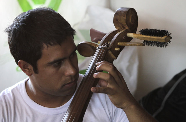 Music student Hugo Irrazabal plays his cello made from recycled materials during a rehearsal of the Orchestra of Recycled Instruments of Cateura, at the Vy'a Renda education center in Cateura, near Asuncion, May 8, 2013. (Photo by Jorge Adorno/Reuters)