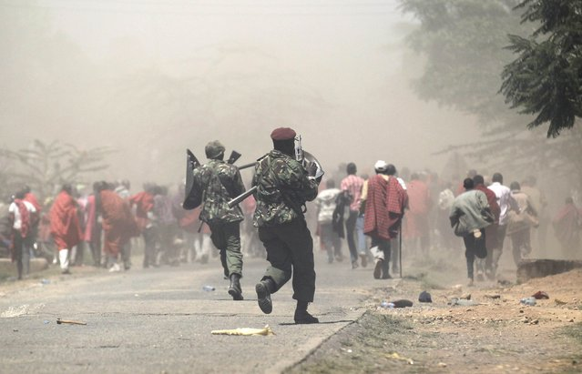 Riot policemen disperse demonstrators during protests to oust Narok county Governor Samuel Tunai in Narok, Kenya, January 26, 2015. (Photo by Thomas Mukoya/Reuters)
