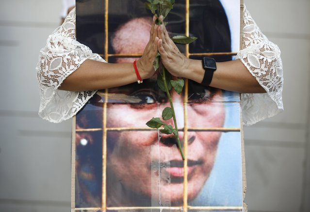 A Myanmar woman living in Thailand holds a rose as she prays for coup ousted detained leader Aung San Suu Kyi during a protest against Indonesian government's alleged support to the junta, at the Indonesian embassy in Bangkok, Thailand, 23 February 2021. Anti-coup protesters gathered to protest following media reports suggesting that Indonesian government is supporting a plan to send observers to Myanmar to ensure that military coup leaders will hold new elections, while protesters are rejecting the suggested plan and want the ousted government to be restored. Myanmar's Aung San Suu Kyi and other top political leaders have been detained after a raid in a military coup due to a tension rising between civilian government and the military disputed from the November 2020 elections results. (Photo by Rungroj Yongrit/EPA/EFE)
