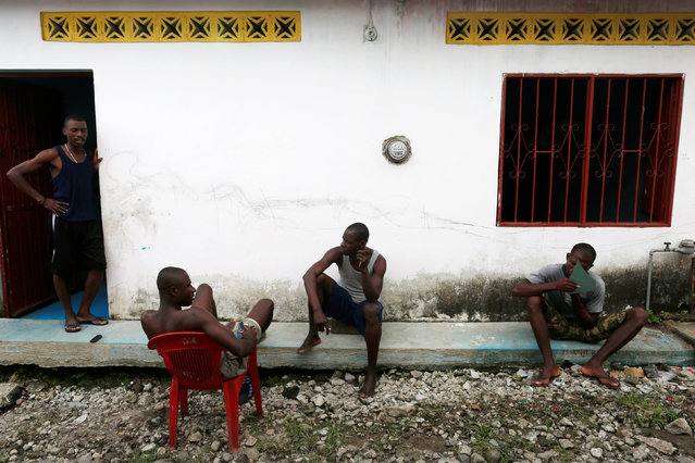Haitian migrants sit outside a house as they wait for money to be sent and continue their journey to the U.S in Tapachula, Chiapas, Mexico November 16, 2016. (Photo by Carlos Jasso/Reuters)