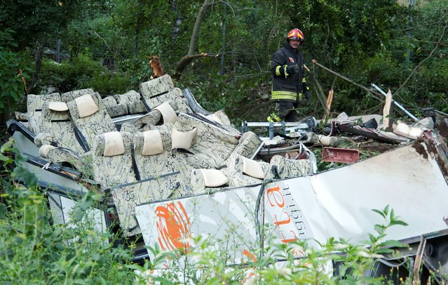 A firefighter looks at the wreckage of a bus which crashed off a highway near Avellino, southern Italy, Monday, July 29, 2013. Rescuers wielding electric saws cut through the twisted wreckage of an Italian tour bus for survivors of a crash in southern Italy that killed at least 37 people after it crashed into traffic and plunged into a ravine on Sunday night. Reports said as many as 49 people, mostly Italians, had been aboard the bus when it ripped through a guardrail, then plunged some 30 meters (100 feet) off a viaduct near a wooded area. (Photo by Salvatore Laporta/AP Photo)