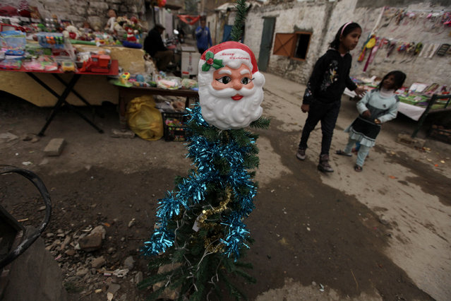 A Santa Claus themed mask is displayed at a stall in a Christian neighborhood slum ahead of Christmas in Islamabad, Pakistan, December 22, 2015. (Photo by Faisal Mahmood/Reuters)