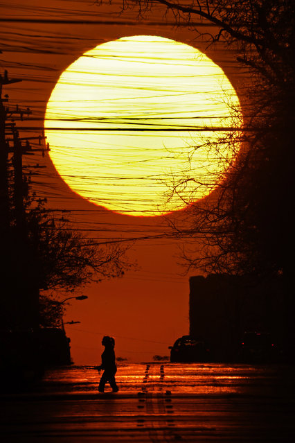 A woman is silhouetted by the setting sun as he crosses a street on the first day of spring Saturday, March 20, 2021, in San Antonio. (Photo by Charlie Riedel/AP Photo)