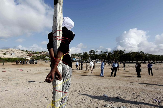 Adan Sheikh Abdi Sheikh, sentenced to death for the murder of journalist Hassan Yusuf Absuge, stands tied to a pole before he is executed by shooting at close range at Iskola Bulisiya Square in Mogadishu, on August 17, 2013. (Photo by Feisal Omar/Reuters)