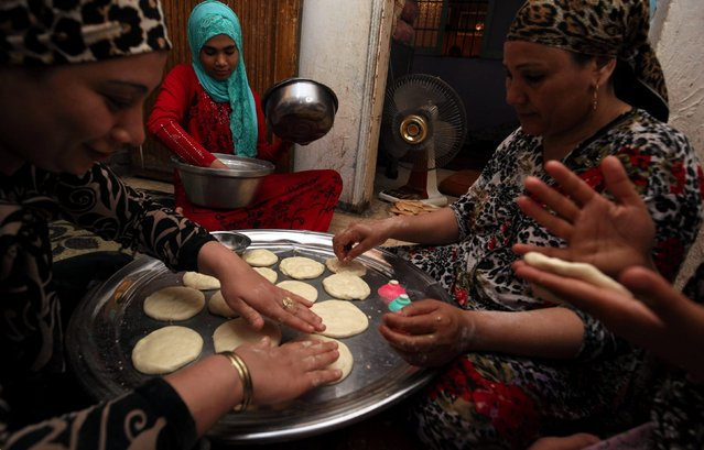 "Egyptian women prepare ""Kahk"", traditional Egyptian butter cookies to celebrate Eid al-Fitr, which marks the end of the holy month of Ramadan, in Cairo, Egypt June 12, 2018. (Photo by Hayam Adel/Reuters)"