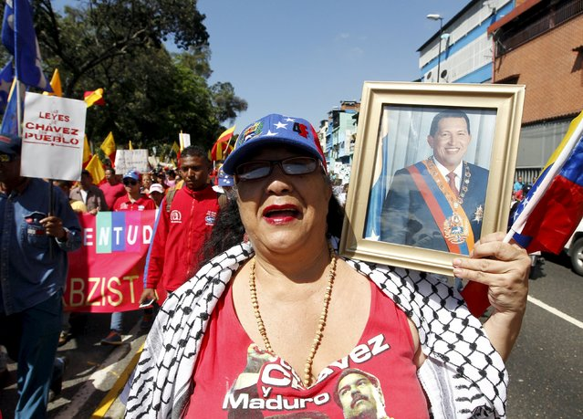 A supporter of Venezuela's President Nicolas Maduro holds a framed photograph of Venezuela's late President Hugo Chavez as she gathers with others some streets away from the building housing the National Assembly in Caracas, January 5, 2016. (Photo by Christian Veron/Reuters)