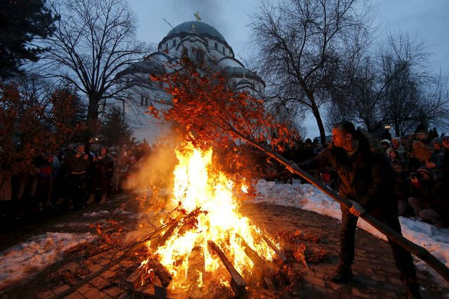 Believers burn dried oak branches, which symbolizes the Yule log, on Orthodox Christmas Eve in front of the St. Sava temple in Belgrade, Serbia, January 6, 2016. (Photo by Marko Djurica/Reuters)