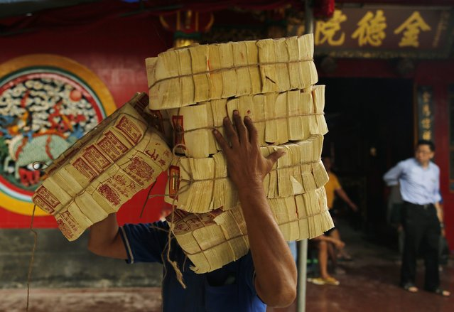 A worker carries offering papers before upcoming Chinese Lunar New Year celebrations, at Petak Sembilan temple in Jakarta, February 17, 2015. (Photo by Reuters/Beawiharta)