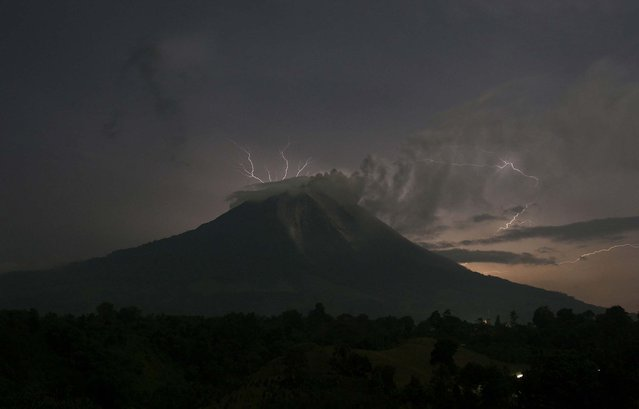 Lightning strikes as Mount Sinabung spews ash and hot lava, at Simpang Empat village in Indonesia's North Sumatra province, on September 18, 2013. (Photo by Y. T. Haryono/Reuters)