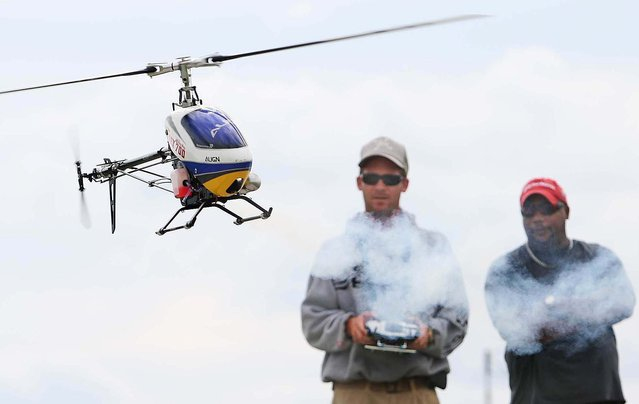 Phil Dettman controls an electric Flybarless 3-axis gyro helicopter doing acrobatic maneuvers while Andrew Wright looks. (Photo by Bill Ingram/The Palm Beach Post)