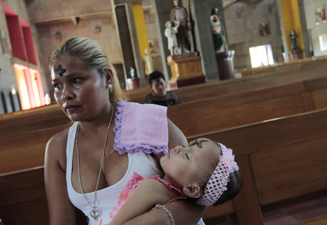 A woman and her daughter sit after receiving crosses of ashes on their foreheads during the traditional Ash Wednesday service at the Metropolitan Cathedral in Managua February 18, 2015. (Photo by Oswaldo Rivas/Reuters)