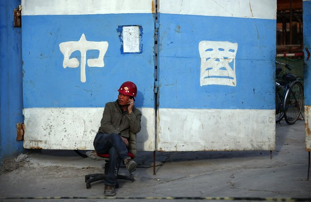 A man talks on his mobile phone outside a construction site in central Beijing, in this October 14, 2013 file photo. Data traffic on Chinese mobile devices jumped almost 50 percent in 2014 but overall usage was modest by global standards, reflecting low consumption in rural areas that hasn't gone unnoticed by telecoms firms. (Photo by Petar Kujundzic/Reuters)