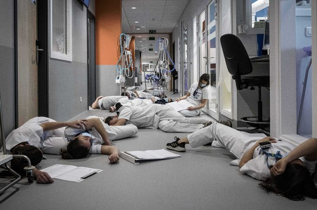 Nursing and care personnel lay on the floor in the ICU unit, during a demonstration on International Nursing and Care day, at the Mont Legia Hospital in Liege, Belgium, Wednesday, May 12, 2021. Hospital personnel around Belgium took part in various actions around the country on Wednesday to highlight the work they do and demand better recognition. (Photo by Valentin Bianchi/AP Photo)
