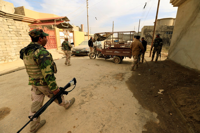 Iraqi soldiers carry weapons during an operation against Islamic State militants in the neighbourhood of Intisar, eastern Mosul, Iraq, December 5, 2016. (Photo by Thaier al-Sudani/Reuters)
