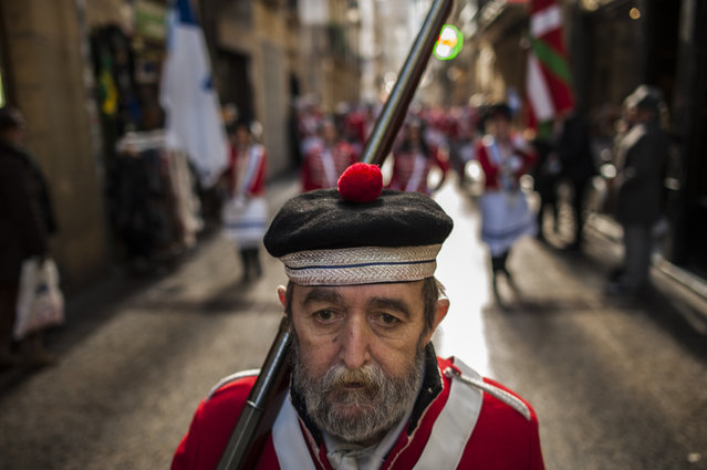 """An old """"Tamborillero'"""" wearing his uniform marchs in the traditional """"La Tamborrada'"""" the big day or """"El Dia Grande"""", the main day of San Sebastian feasts, in the Basque city of San Sebastian, northern Spain, Wednesday January 20, 2016. From midnight to midnight companies of perfectly uniformed marchers parade through the streets of San Sebastian playing drums and barrels in honor of their patron saint. (Photo by Alvaro Barrientos/AP Photo)"""
