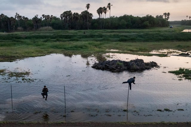 Migrants from Central America jump a fence as they run south towards Mexico while being chased by a U.S. border patrol agent after crossing the Rio Grande river into the United States from Mexico in La Joya, Texas, U.S., May 23, 2021. (Photo by Adrees Latif/Reuters)