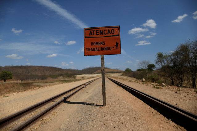 """A sign which reads """"Take care men working"""" stands along the construction of the Transnordestina railway track in Missao Velha, Ceara state, Brazil, October 25, 2016. (Photo by Ueslei Marcelino/Reuters)"""