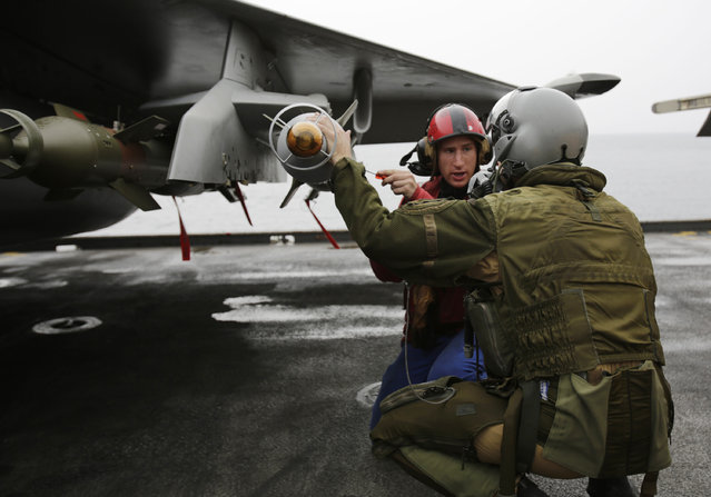 In this Wednesday, March 18, 2015 photo, a French pilot checks the bombs on his military plane before taking off from the flight deck of the French Navy aircraft carrier Charles de Gaulle in the Persian Gulf. (Photo by Hasan Jamali/AP Photo)