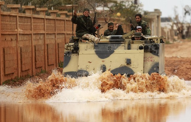 Members of the Libyan pro-government forces, backed by the locals, ride in a military vehicle during clashes in the streets with the Shura Council of Libyan Revolutionaries, an alliance of former anti-Gaddafi rebels who have joined forces with Islamist group Ansar al-Sharia, in Benghazi March 16, 2015. (Photo by Esam Omran Al-Fetori/Reuters)