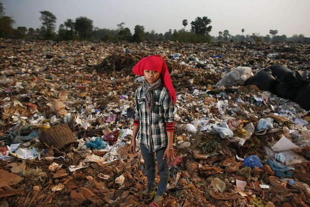 Chenda, a 15-year-old girl, poses for a picture after collecting usable items at a landfill dumpsite outside Siem Reap March 19, 2015. An eight-grade student, she sometimes misses school to work at the dumpsite where her family lives. (Photo by Athit Perawongmetha/Reuters)