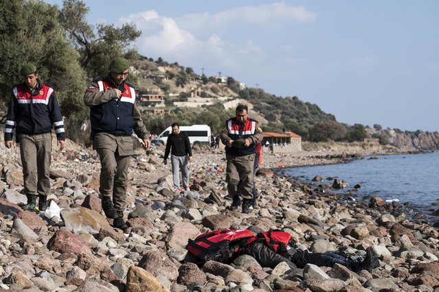 Turkish paramilitary police officers stand near a dead body of a migrant on the beach near the Aegean town of Ayvacik, Canakkale, Turkey, Saturday, January 30, 2016. (Photo by Halit Onur Sandal/AP Photo)