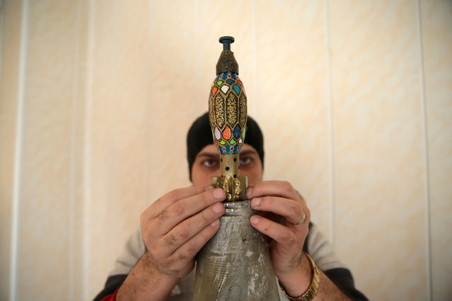 Akram Abu al-Foz places a painted empty shell on top of a Christmas tree he decorated from empty shells he collected in the rebel held besieged city of Douma, in the eastern Damascus suburb of Ghouta, Syria December 23, 2016. (Photo by Bassam Khabieh/Reuters)