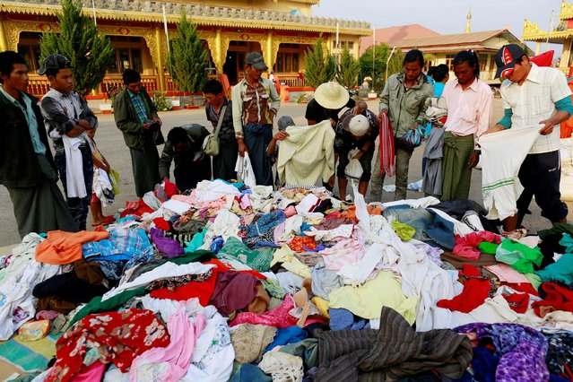 Newly arrived refugee choose clothes in temporary refugee camp at a monastery, in Lashio February 19, 2015. (Photo by Soe Zeya Tun/Reuters)