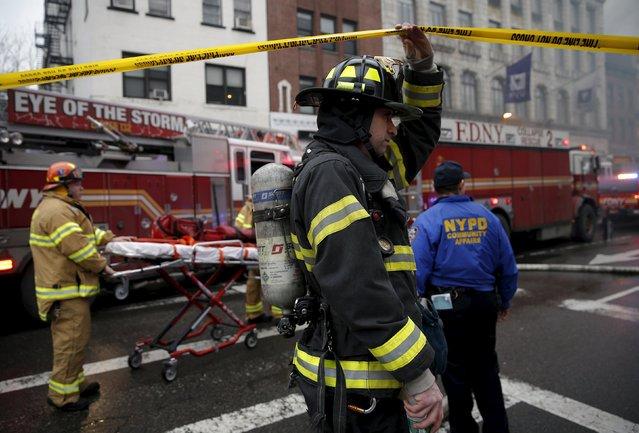 New York City Fire Department firefighters walk towards the site of a residential apartment building collapse and fire in New York City's East Village neighborhood March 26, 2015. (Photo by Mike Segar/Reuters)