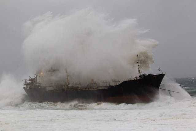 A wave crashes into a ship which broke free from a tow line at Sheffield Beach some 60km (37 miles) north of Durban, South Africa, July 26, 2011. The ship subsequently ran aground. (Photo by Rogan Ward/Reuters)