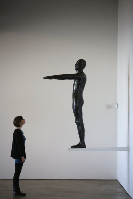 """A gallery staff member views Untitled (Diving Figure) by Antony Gormley, one of the works on display at in Yorkshire Sculpture Parks Longside Gallery as part of the """"Making It: Sculpture in Britain 1977-1986"""" exhibition on March 27, 2015 in Barnsley, England. (Photo by Christopher Furlong/Getty Images)"""