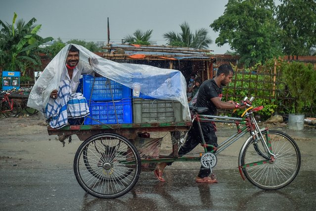 A man wraps a plastic sheet to shelter from the rain while sitting on a cycle-rickshaw cart during a downpour in Dhaka on June 21, 2021. (Photo by Munir Uz Zaman/AFP Photo)