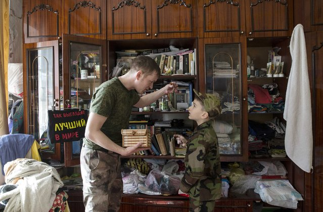 Valery, 30, a member of the People's Militia of Crimea, shows his son Kirill a medal, which was presented to Valery for merits while serving in a self-defence unit, inside his house on the first anniversary of the Crimean referendum to secede from Ukraine and join Russia, in Simferopol, March 16, 2015. (Photo by Maxim Shemetov/Reuters)