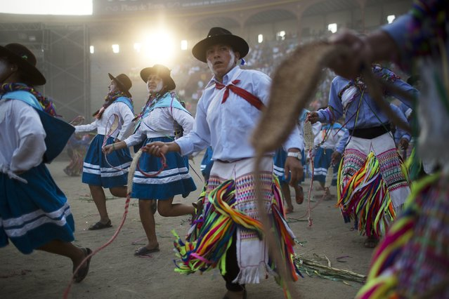 In this Sunday, March 29, 2015 photo, a dance troupe from La Mar district of Ayacucho performs during the Vencedores de Ayacucho dance festival, in the Acho bullring in Lima, Peru. (Photo by Rodrigo Abd/AP Photo)