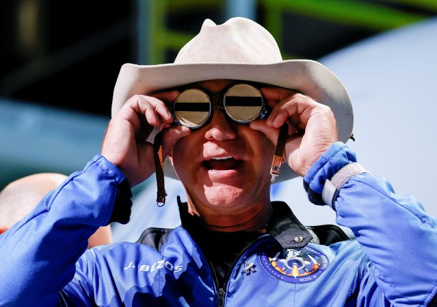 Billionaire American businessman Jeff Bezos wears goggles owned by Amelia Earhart which he carried into space at a post-launch press conference after he flew on Blue Origin's inaugural flight to the edge of space, in the nearby town of Van Horn, Texas, U.S. July 20, 2021. (Photo by Joe Skipper/Reuters)