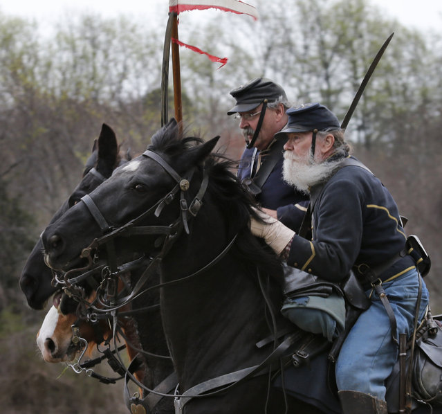 Union re-enactors charge the Confederate lines during a re-enactment of the Battle of Appomattox Station, Wednesday, April 8, 2015, as part of the 150th anniversary of the surrender of the Army of Northern Virginia to Union forces at Appomattox Court House, in Appomattox, Va. (Photo by Steve Helber/AP Photo)
