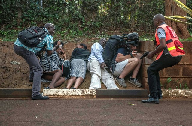 People take cover after hearing gunfire coming from the Dusit Hotel complex after being rescued on January 15, 2018 in Nairobi, Kenya. A current security operation is underway after terrorists attacked the hotel. (Photo by Andrew Renneisen/Getty Images)
