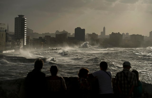 Tourists watch the strong waves breaking over the Malecon seawall as a result of heavy winds flooding urban areas in Havana, Cuba, Friday, December 21, 2018. (Photo by Ramon Espinosa/AP Photo)